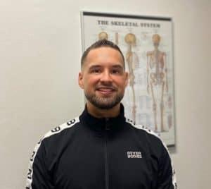 En glad og smilende portræt billede af Fysioterapeut René Nørgaard, i baggrunden kan man se en anatomi plakat over skelettet.
