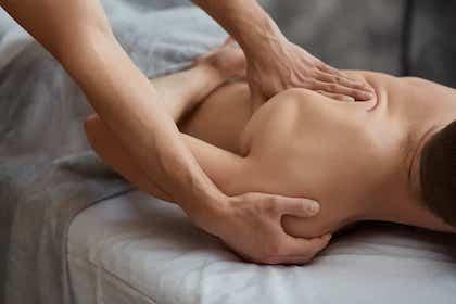 En mandlig patient ligger ned og får fysioterapi behandling under det høre skulderblad af en fysioterapeut.