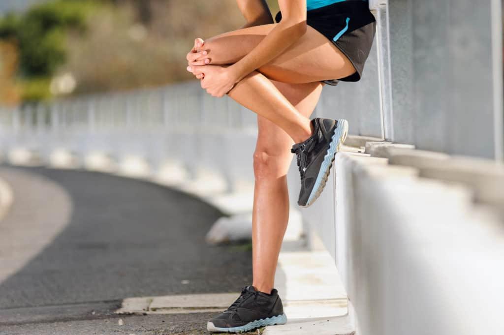 En kvindelig løber i smerte, tager sig til knæet med begge hænder.