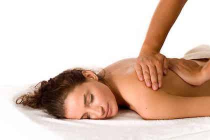 En kvindelig patient ligger på maven, på et hvidt håndklæde. Hun smiler imens hun får behagelig massage på ryggen af en fysioterapeut.