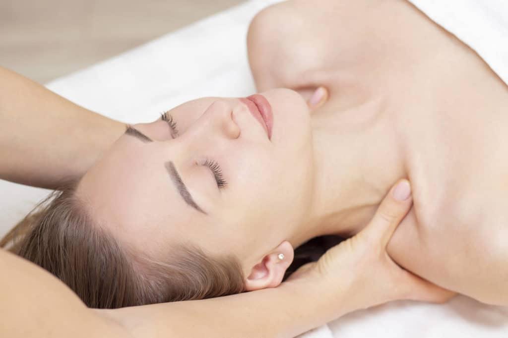 En kvinde ligger på ryggen og smiler. Hun får wellness behandling af en fysioterapeut der har begge hænder under hendes nakke.