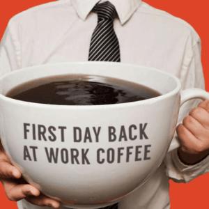 """Mand som holder en kæmpe stor kop kaffe. På koppen står der. """" First Day Back at Work Coffee."""